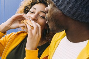 African man and latin woman eating h