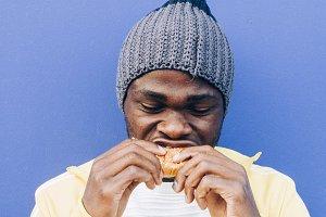 African man eating hamburger togethe