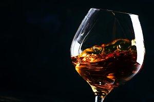 Cognac in a glass, dark background,