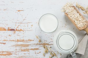 Oat milk in glass and jar on wood