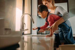 Little boy with mother washing hands