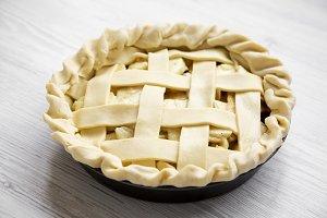Apple pie on white wooden background