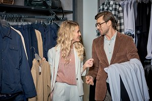 couple holding stylish clothes and s
