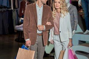 smiling stylish couple holding shopp