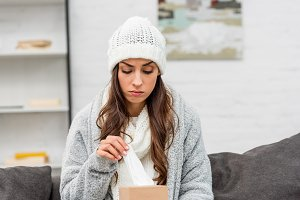 depressed sick woman in warm clothes
