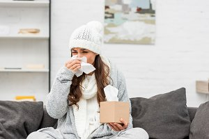 sick young woman in warm clothes blo