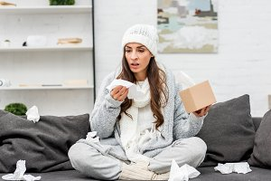 sick young woman in warm clothes sit