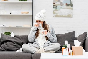 sick young woman in warm clothes sne