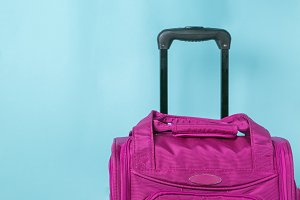 Traveling concept - pink suitcase in