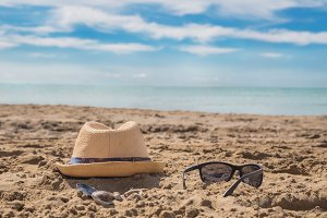 Sunglass and cap on sand against
