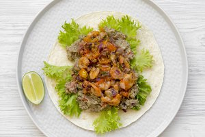 Shrimp taco with lime on round gray