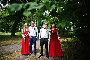 Bridesmaids at red dresses with groo