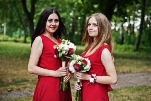 Two girls bridesmaids at red dresses