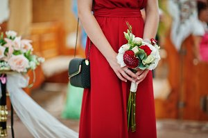 Hands of bridesmaids at red dresses