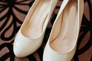 White wedding shoes of bride at text