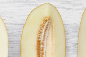 Melon slices on white wooden table