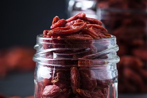 Goji berries in glass jar, dark wood