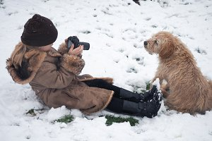 The child takes pictures of the dog