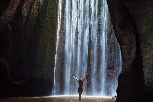 Woman stand under cave waterfall