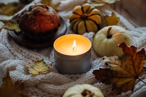 Burning candle in jar, autumn leaves