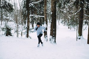 Young man running in snowy area