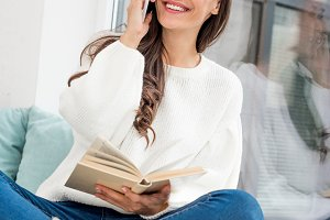 happy young woman reading book and t