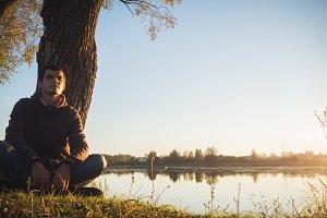 A young man doing yoga at sunset nea