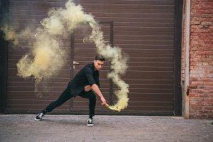 young man dancing in yellow smoke on