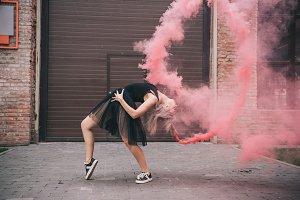 flexible girl dancing in pink smoke