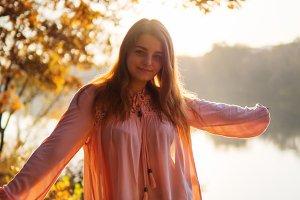 Beautiful cute girl on autumn sunset