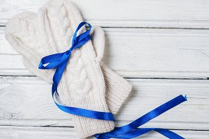 White mittens with blue ribbon on wh