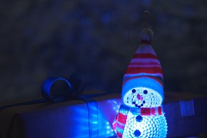 Snowman toy and gift in the dark at