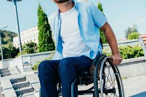 handsome man in wheelchair looking u