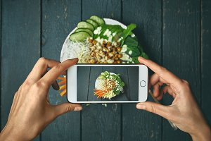 woman taking pictures of buddha bowl