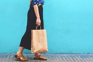 Young woman walking with shopping ba