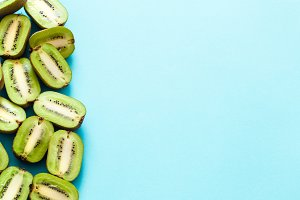 Fresh halves of kiwi on a blue backg