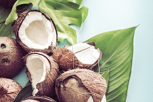 Coconut with tropical leaves on a bl