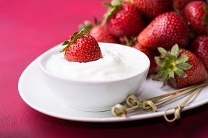 Strawberry in a bowl with cream