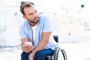 handsome man in wheelchair listening
