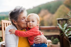 Elderly woman kissing a toddler