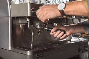 cropped shot of barista using coffee