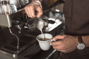 cropped shot of barista pouring milk