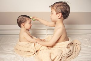 Boy combing little girl after bath