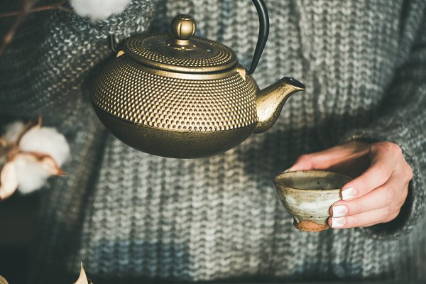 Female pouring green tea from golde…