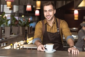 handsome young barista with cup of d
