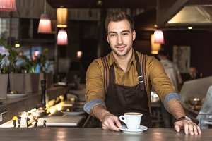 attractive young barista with cup of