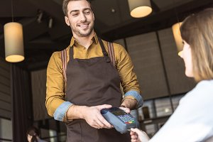 happy young waiter holding payment t
