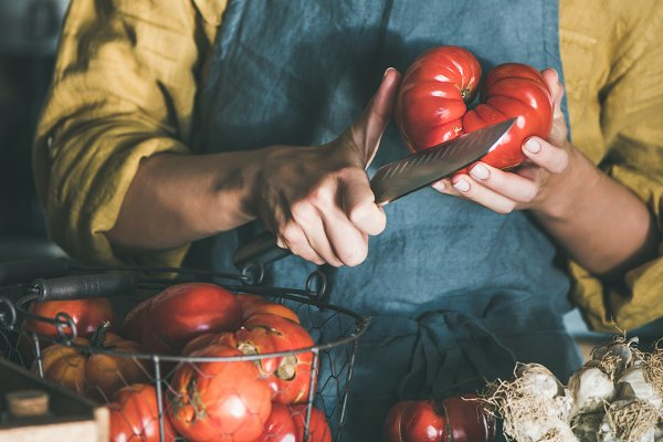 Woman in linen apron cutting ripe