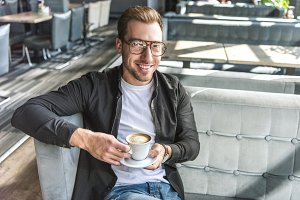 smiling young man with cup of coffee