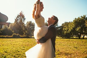 Dancing young bride and groom sunlig